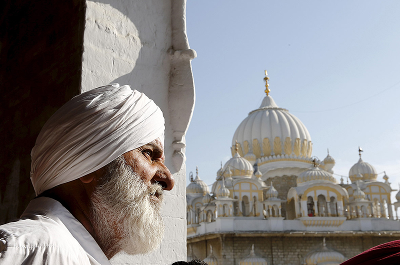 A Sikh devotees watches the Vaisakhi festival procession at Panja Sahib shrine in Hassan Abdel, Pakistan