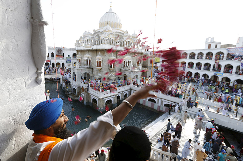 A Sikh devotee throws petals as the procession passes by during the Vaisakhi festival at Panja Sahib shrine in Hassan Abdel