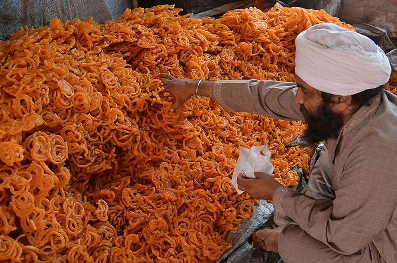 A man puts sweets into plastic bags for free distribution to devotees during the Vaisakhi festival celebrations at the Golden Temple in Amritsar