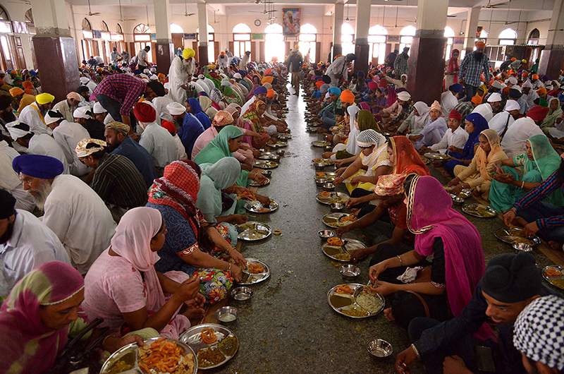 Indian Sikh devotees eat a communal vegetarian meal at Langar Ghar, a community hall at the Golden Temple in Amritsar