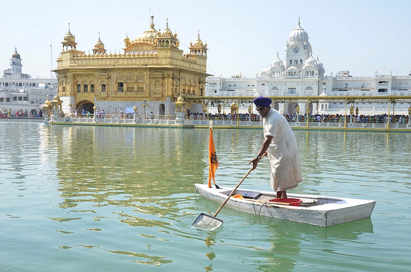 A man cleans the holy sarover (water tank) at the Golden Temple in Amritsar